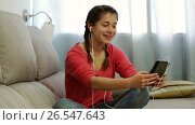 Купить «Young woman using the phone to listen to music at home», видеоролик № 26547643, снято 18 апреля 2017 г. (c) Яков Филимонов / Фотобанк Лори