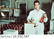 Купить «Man standing in packing section on winemaking factory», фото № 26550347, снято 21 сентября 2016 г. (c) Яков Филимонов / Фотобанк Лори