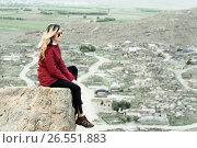 Купить «Грустная девушка сидит на фоне горных дорог», фото № 26551883, снято 11 мая 2017 г. (c) Эдуард Паравян / Фотобанк Лори