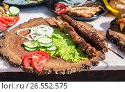 Купить «Grilled shish kebab or shashlik on wooden skewers with fresh vegetables», фото № 26552575, снято 11 июня 2017 г. (c) FotograFF / Фотобанк Лори