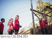 Купить «Trainer assisting a kid to climb a rope in the boot camp», фото № 26554351, снято 16 марта 2017 г. (c) Wavebreak Media / Фотобанк Лори