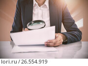 Composite image of businesswoman looking at document through magnifying glass. Стоковое фото, агентство Wavebreak Media / Фотобанк Лори