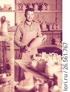 Купить «happy man potter holding ceramic vessels», фото № 26561767, снято 20 октября 2018 г. (c) Яков Филимонов / Фотобанк Лори