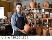 Купить «man potter holding ceramic vessels in atelier», фото № 26561831, снято 20 октября 2018 г. (c) Яков Филимонов / Фотобанк Лори