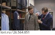 Купить «Tailor measures a man in the atelier», видеоролик № 26564851, снято 5 июня 2017 г. (c) Raev Denis / Фотобанк Лори