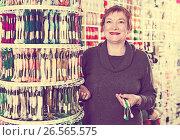 Купить «Woman choosing mouline for embroidery in needlework shop», фото № 26565575, снято 10 мая 2017 г. (c) Яков Филимонов / Фотобанк Лори