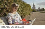Купить «Girl in the fresh air typing on the keyboard of a white laptop. Young sophisticated woman using a laptop outdoors.», видеоролик № 26566035, снято 9 июня 2017 г. (c) Mikhail Davidovich / Фотобанк Лори