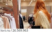 Купить «Attractive girl in a fashion dress store chose a clothe - shopping concept», видеоролик № 26569963, снято 18 января 2020 г. (c) Константин Шишкин / Фотобанк Лори