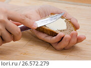 Купить «Руки намазывают сливочное масло на кусок ржаного хлеба», фото № 26572279, снято 25 февраля 2016 г. (c) Павел Родимов / Фотобанк Лори