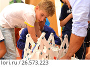 """SOCHI, RUSSIA - June 24, 2017: A schoolboy with a teacher completes the construction of a robot in an open lesson of the All-Russian Educational Center """"Sirius"""" Редакционное фото, фотограф Анна Мартынова / Фотобанк Лори"""