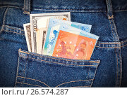 Different banknotes of Euro and american currency sticking out of the back jeans pocket. Money in jeans pocket for travel and shopping, фото № 26574287, снято 20 июля 2017 г. (c) FotograFF / Фотобанк Лори