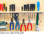 Different screwdrivers and pliers on a yellow chipboard, фото № 26574291, снято 21 июля 2017 г. (c) FotograFF / Фотобанк Лори