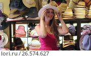 Купить «young happy blond woman choose straw hat in shop», видеоролик № 26574627, снято 16 мая 2017 г. (c) Яков Филимонов / Фотобанк Лори
