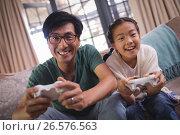 Купить «Father and daughter playing video game in living room», фото № 26576563, снято 20 марта 2017 г. (c) Wavebreak Media / Фотобанк Лори