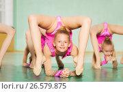 Купить «Young girl practicing rhythmic gymnastics in gym», фото № 26579875, снято 16 апреля 2017 г. (c) Сергей Новиков / Фотобанк Лори