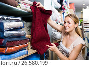 Купить «Portrait of laughing woman choosing blanket», фото № 26580199, снято 16 июня 2019 г. (c) Яков Филимонов / Фотобанк Лори