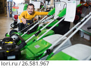 Купить «Man choosing lawnmower», фото № 26581967, снято 2 марта 2017 г. (c) Яков Филимонов / Фотобанк Лори