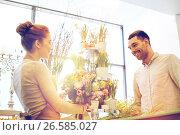 Купить «smiling florist woman and man at flower shop», фото № 26585027, снято 27 марта 2016 г. (c) Syda Productions / Фотобанк Лори