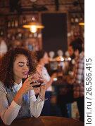 Купить «Young woman having red wine in pub», фото № 26586415, снято 14 ноября 2016 г. (c) Wavebreak Media / Фотобанк Лори