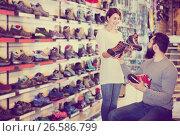 Купить «Couple deciding on new sneakers», фото № 26586799, снято 24 февраля 2017 г. (c) Яков Филимонов / Фотобанк Лори