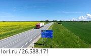 Купить «Грузовой автомобиль едет по трассе Е20 Нарва-Таллин. Дорожный знак у указанием расстояний до городов. Эстония», видеоролик № 26588171, снято 27 июня 2017 г. (c) Кекяляйнен Андрей / Фотобанк Лори