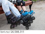 Купить «Роликовые коньки на ногах женщины и ребенка, люди сидят на скамейке», фото № 26588311, снято 18 июня 2017 г. (c) Кекяляйнен Андрей / Фотобанк Лори