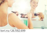 Купить «woman with makeup brush and foundation at bathroom», фото № 26592699, снято 13 февраля 2016 г. (c) Syda Productions / Фотобанк Лори