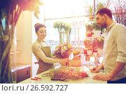 Купить «smiling florist woman and man at flower shop», фото № 26592727, снято 27 марта 2016 г. (c) Syda Productions / Фотобанк Лори