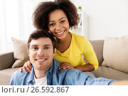 Купить «happy multiethnic couple taking selfie at home», фото № 26592867, снято 4 февраля 2017 г. (c) Syda Productions / Фотобанк Лори