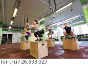 Купить «group of people doing box jumps exercise in gym», фото № 26593327, снято 19 февраля 2017 г. (c) Syda Productions / Фотобанк Лори