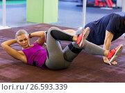 Купить «woman with man doing curl ups and push ups in gym», фото № 26593339, снято 19 февраля 2017 г. (c) Syda Productions / Фотобанк Лори