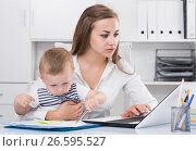 Купить «Serious mother with kid is сoncentratedly working behind laptop», фото № 26595527, снято 13 июня 2017 г. (c) Яков Филимонов / Фотобанк Лори