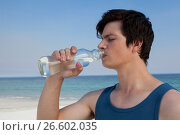Купить «Man drinking water from bottle at beach», фото № 26602035, снято 17 января 2017 г. (c) Wavebreak Media / Фотобанк Лори