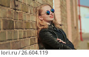 Купить «Stylish young blonde in sunglasses and black leather jacket near a brick wall on the street», видеоролик № 26604119, снято 12 мая 2017 г. (c) Mikhail Davidovich / Фотобанк Лори