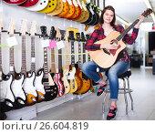 Купить «Charming female teenager examining various acoustic guitars», фото № 26604819, снято 14 февраля 2017 г. (c) Яков Филимонов / Фотобанк Лори