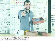 Купить «Man seller going through boxes with door», фото № 26605211, снято 5 апреля 2017 г. (c) Яков Филимонов / Фотобанк Лори