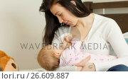Mother breast feeding her baby on bed. Стоковое видео, агентство Wavebreak Media / Фотобанк Лори