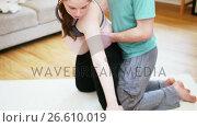 Купить «Man assisting pregnant woman in practicing yoga», видеоролик № 26610019, снято 18 июля 2019 г. (c) Wavebreak Media / Фотобанк Лори