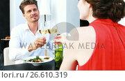 Купить «Couple toasting wine glasses while having lunch in a restaurant», видеоролик № 26610319, снято 18 июля 2019 г. (c) Wavebreak Media / Фотобанк Лори