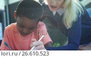 Купить «Teacher helping schoolboy with his homework in classroom», видеоролик № 26610523, снято 4 апреля 2020 г. (c) Wavebreak Media / Фотобанк Лори