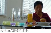 Купить «Senior woman having breakfast», видеоролик № 26611119, снято 18 июля 2019 г. (c) Wavebreak Media / Фотобанк Лори