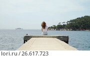 Купить «Woman is sitting on pier in island bay», видеоролик № 26617723, снято 22 июня 2017 г. (c) Илья Насакин / Фотобанк Лори