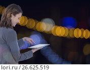 Купить «Smiling woman using a digital tablet with spotlights», фото № 26625519, снято 20 марта 2019 г. (c) Wavebreak Media / Фотобанк Лори
