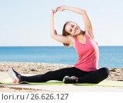 Купить «Happy young woman doing gymnastics exercises», фото № 26626127, снято 17 июля 2019 г. (c) Яков Филимонов / Фотобанк Лори