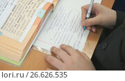 Student writes in a workbook with a ballpoint pen. Стоковое видео, видеограф worker / Фотобанк Лори