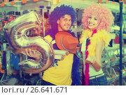 Купить «Couple is having fun in colorful clown wigs», фото № 26641671, снято 11 апреля 2017 г. (c) Яков Филимонов / Фотобанк Лори