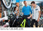Купить «father with son and female seller in bike store», фото № 26645235, снято 27 сентября 2016 г. (c) Яков Филимонов / Фотобанк Лори