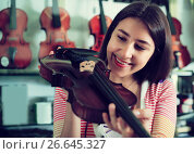 Купить «Girl choosing violin in music shop», фото № 26645327, снято 18 января 2019 г. (c) Яков Филимонов / Фотобанк Лори