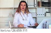 Купить «Young and smiling nurse in uniform filling up documents», видеоролик № 26659111, снято 17 апреля 2017 г. (c) Яков Филимонов / Фотобанк Лори