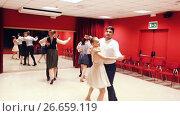 Купить «Young smiling people having dancing class in studio», видеоролик № 26659119, снято 26 июня 2017 г. (c) Яков Филимонов / Фотобанк Лори